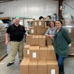 Three people stand in a warehouse with boxes of food